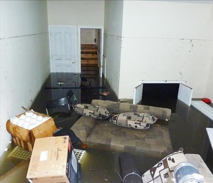 Flooded basement, there is a couch, chair and boxes floating in the water